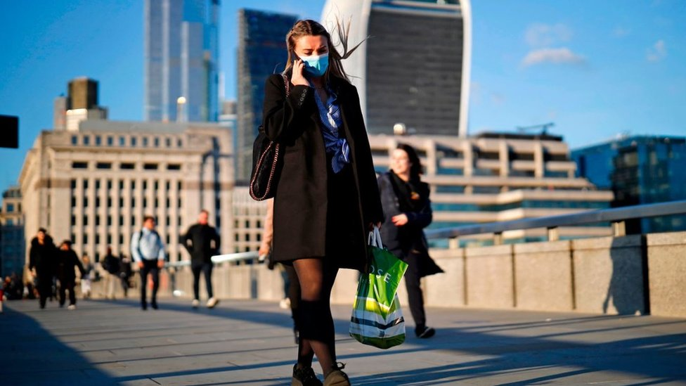A woman wearing a protective face mask speaks on the phone as she crosses London Bridge