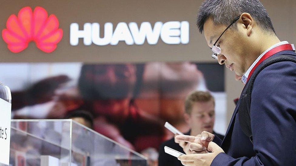 Un hombre viendo a un teléfono de Huawei.
