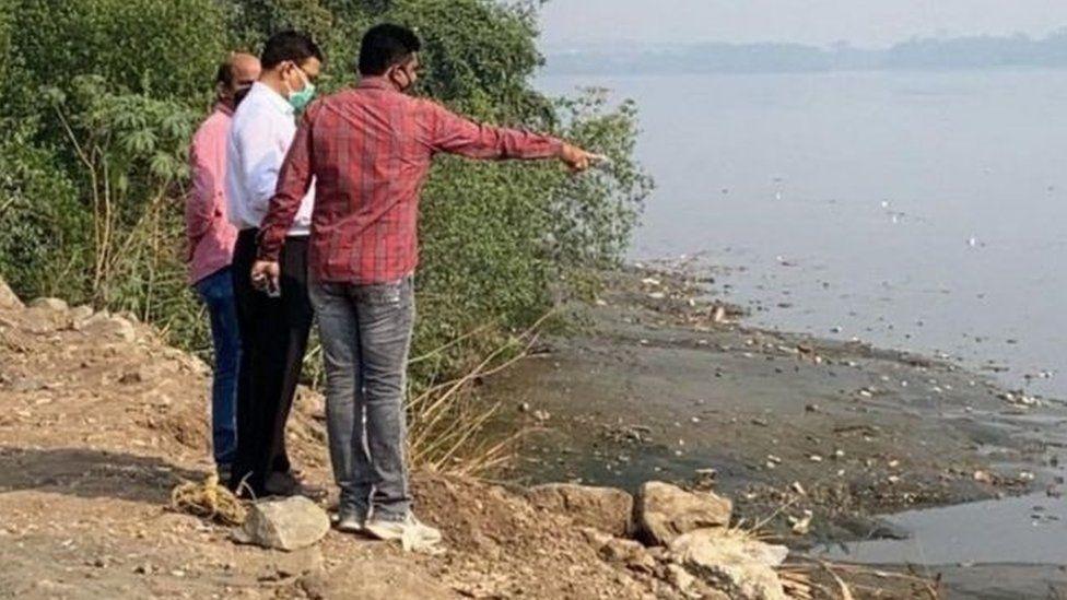Varios hombres apuntan al sitio a orillas de un arroyo donde fue hallado el cuerpo de Hiren