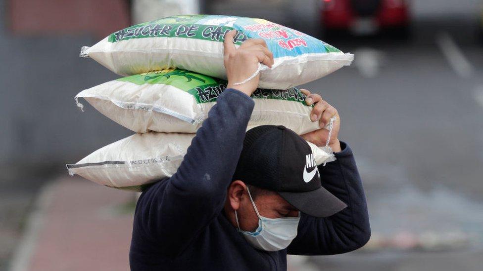 Trabajador cargando un saco en Quito