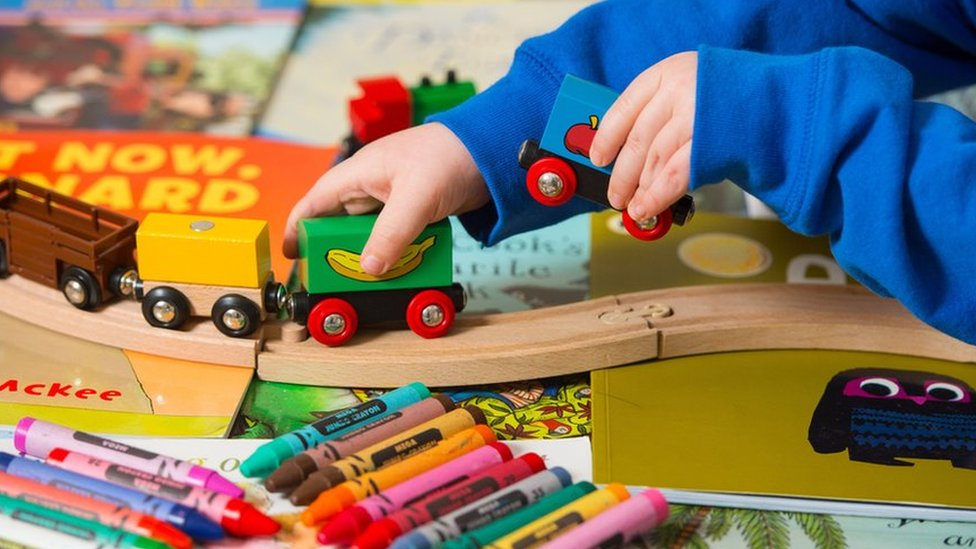 Child playing with wooden train set