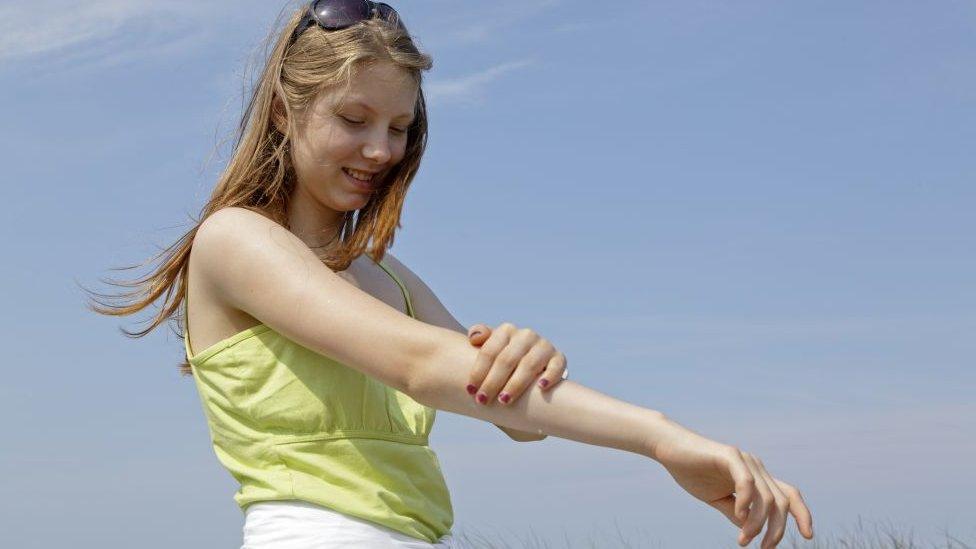 Devojka nanosi kremu za sunčanje