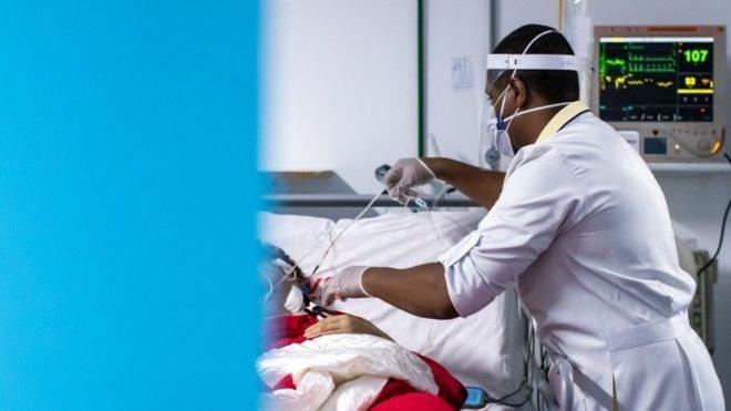 Profissional de saúde atende paciente em maca