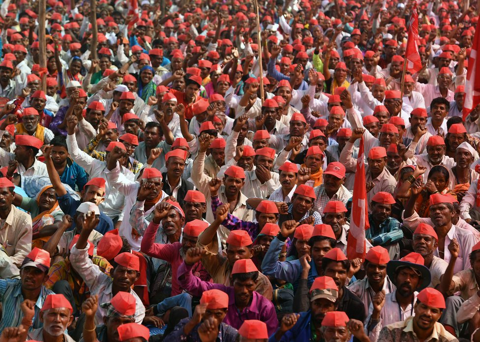 Farmers shout slogans as they listen to speakers during the protest.