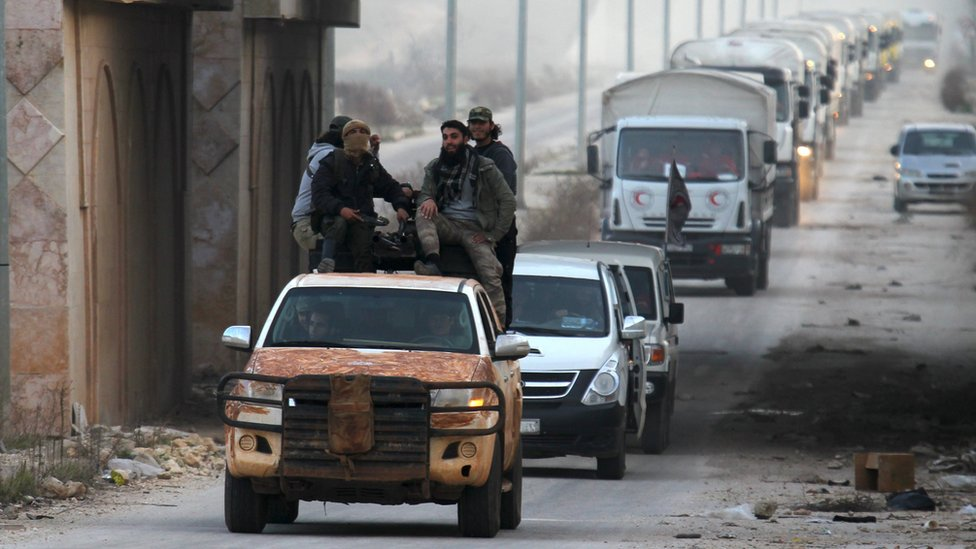 Rebel fighters accompany UN and Syrian Red Arab Crescent aid lorries to the besieged towns of Foah and Kefraya, in Idlib province, Syria (17 February 2016)