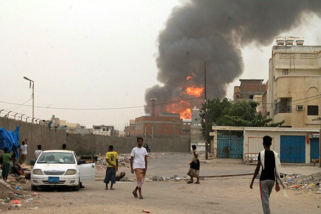 Yemenis watch as smoke billows following clashes between fighters loyal to exiled President Abdrabbuh Mansour Hadi and Houthi rebels in Aden