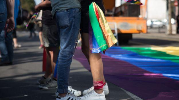 Par se grli, devojka nosi LGBT zastavu