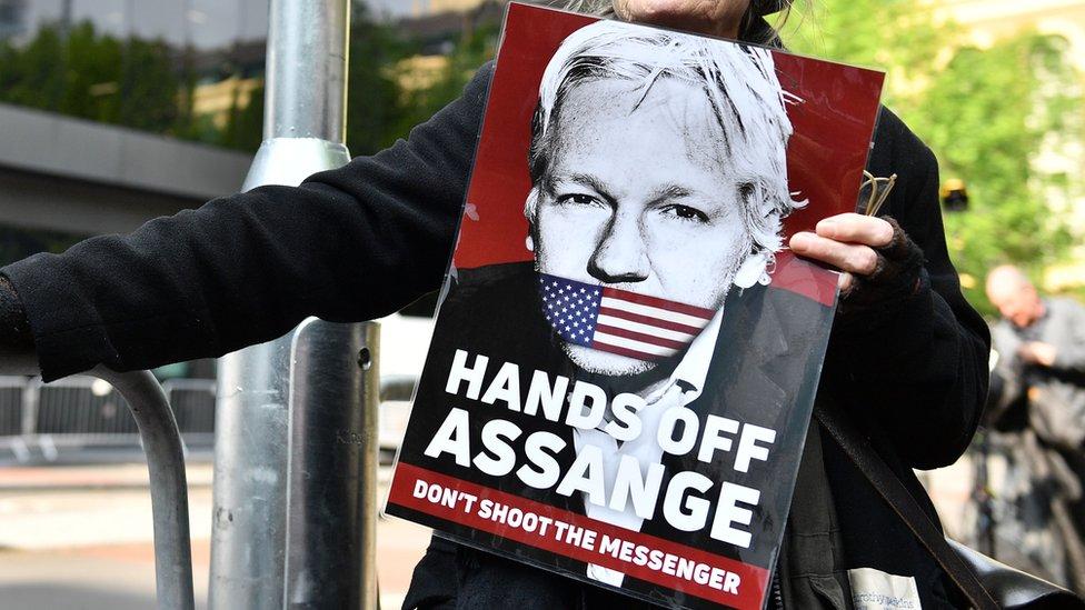 """Una mujer sostiene un cartel que dice: """"saquen las manos de Assange, no disparen al mensajero""""."""