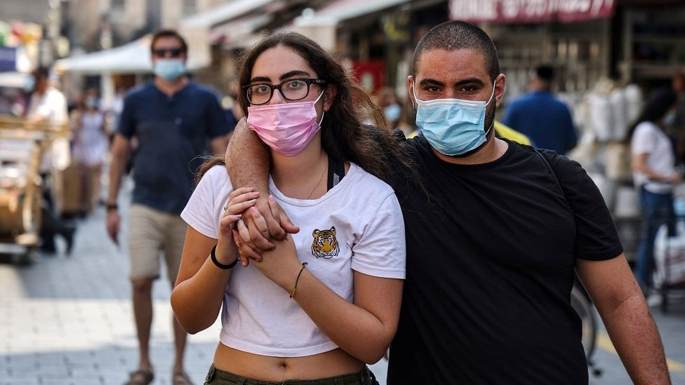 A masked couple strolls in Mahane Yehuda Market in Jerusalem the day before Rosh Hashana on September 17th