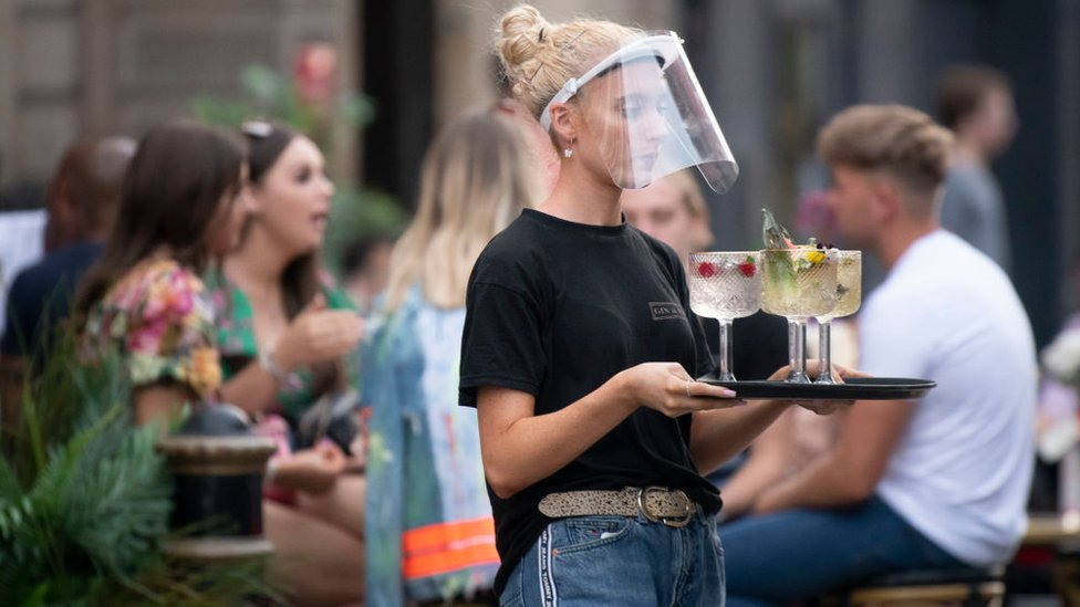 Girl carrying tray in pub