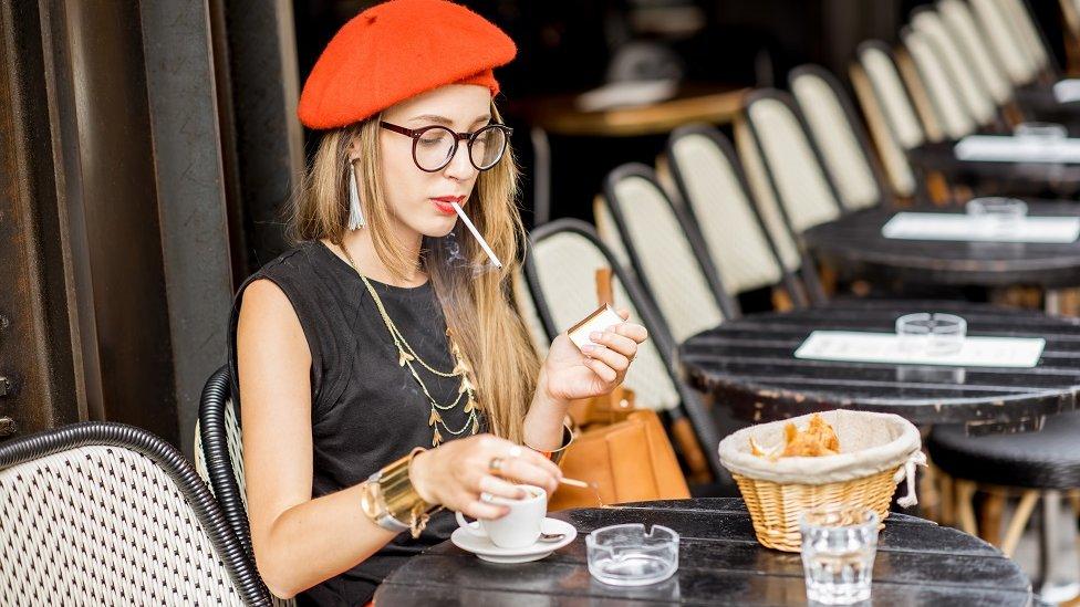 Mujer fumando en un café.