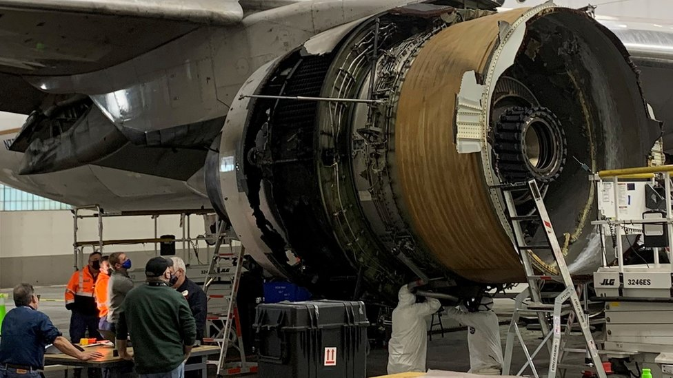 Workers look at the damaged engine on the plane at Denver airport on 22 February 2021