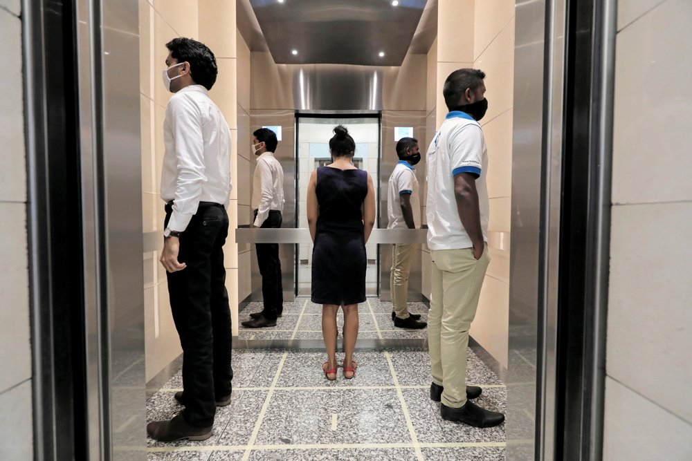 People face away from each other as they practise social distancing inside a lift