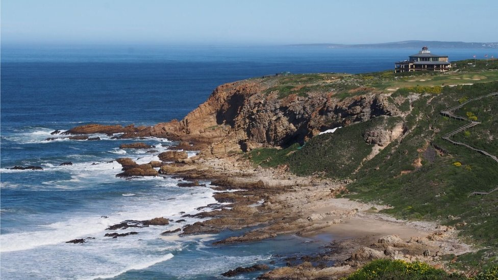 A jagged coastline by the sea. Tarpaulin is just visible behind a ridge, indicating the location of the dig site