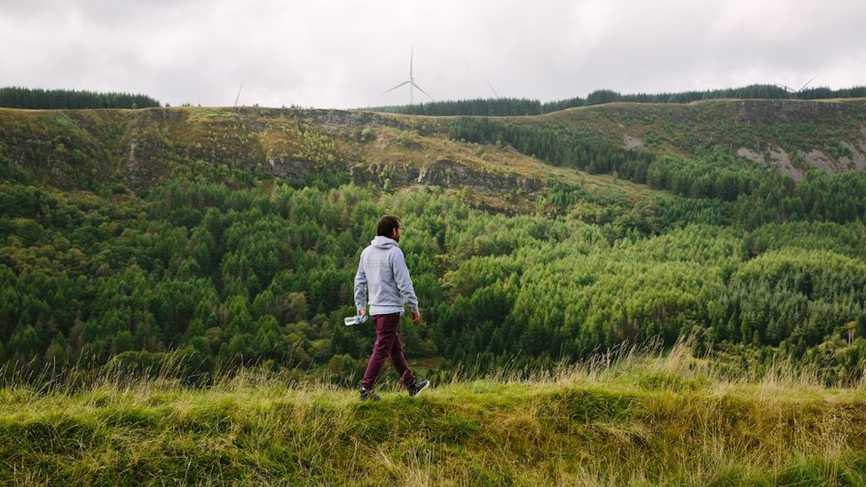 Ian Thomas walking on a hill