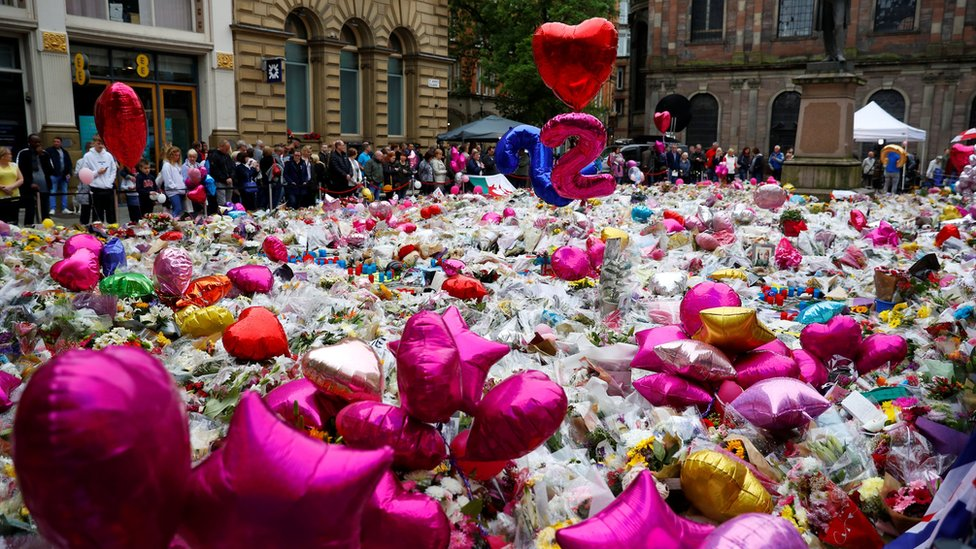 People look at flowers and tributes left in Manchester - a week after the terror attack took place