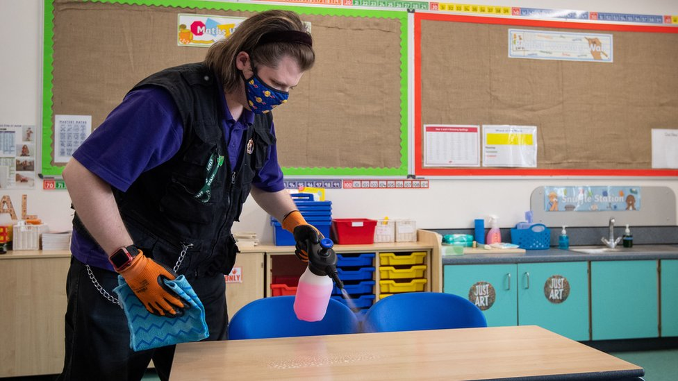 A member of staff disinfects tables at a primary school