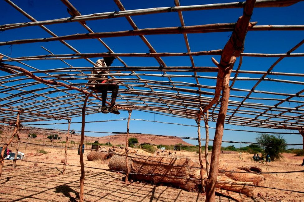 A man uses bamboo and timbre to construct the roof of his temporary home on 15 November.