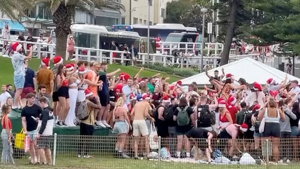 The crowd of backpackers, many wearing Santa hats, at Bronte Beach on Christmas Day