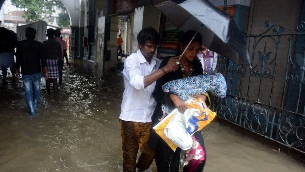 An Indian couple shelter under an umbrella as they walk with their child through floodwaters inundating Egmore Hospital in Chennai on December 1, 2015,