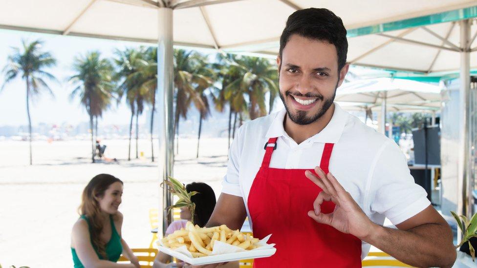 camarero sirviendo papas fritas