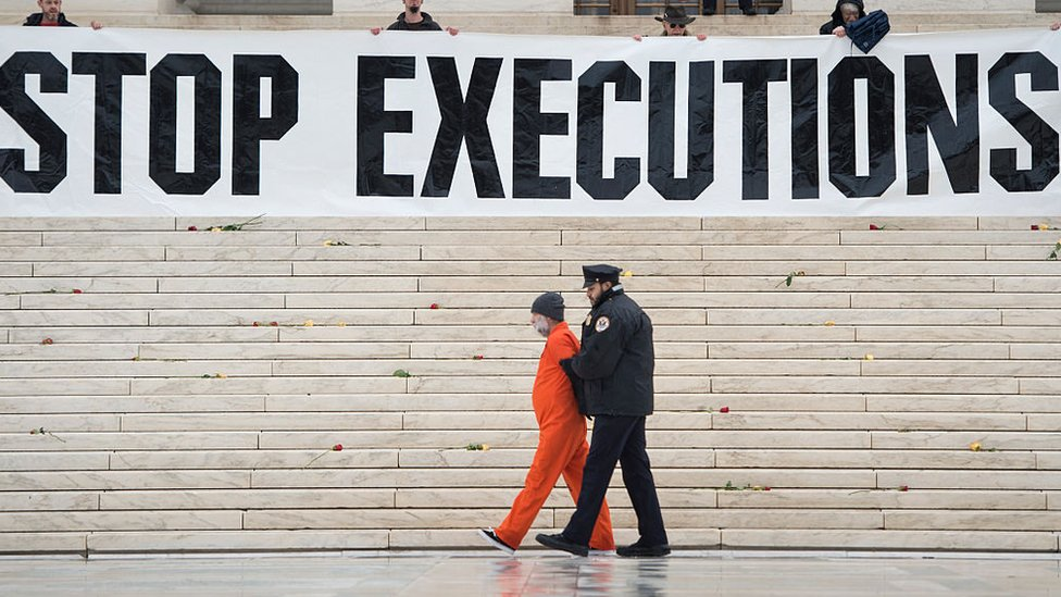 """Protesters erecting a large banner reading """"stop executions"""" outside the US Supreme Court in 2017"""