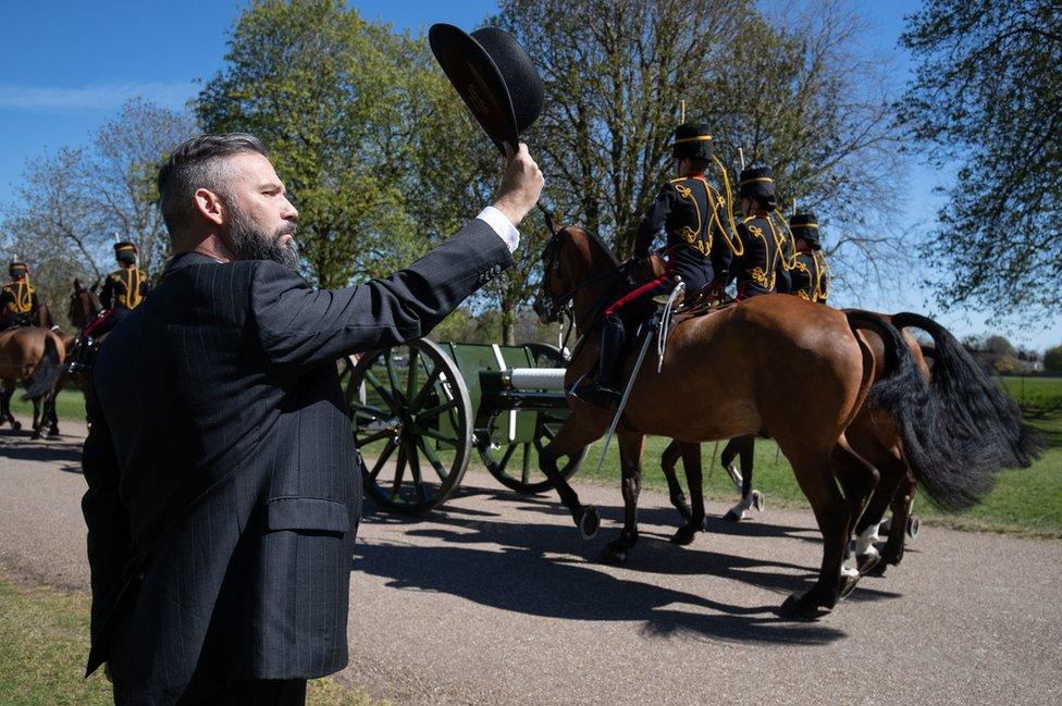 Un hombre se quita el sombrero ante el paso de la artillería durante el funeral del príncipe Felipe