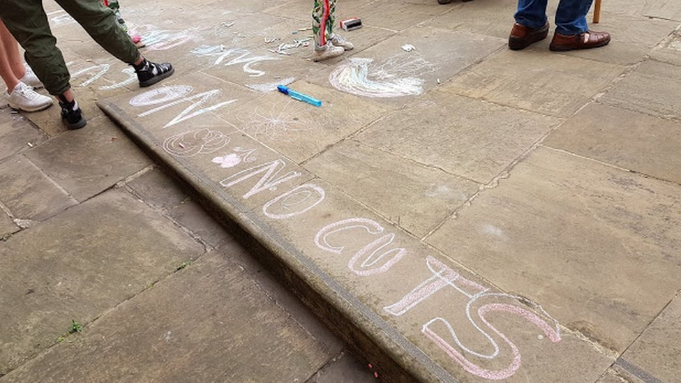 Chalk protest messages outside the meeting