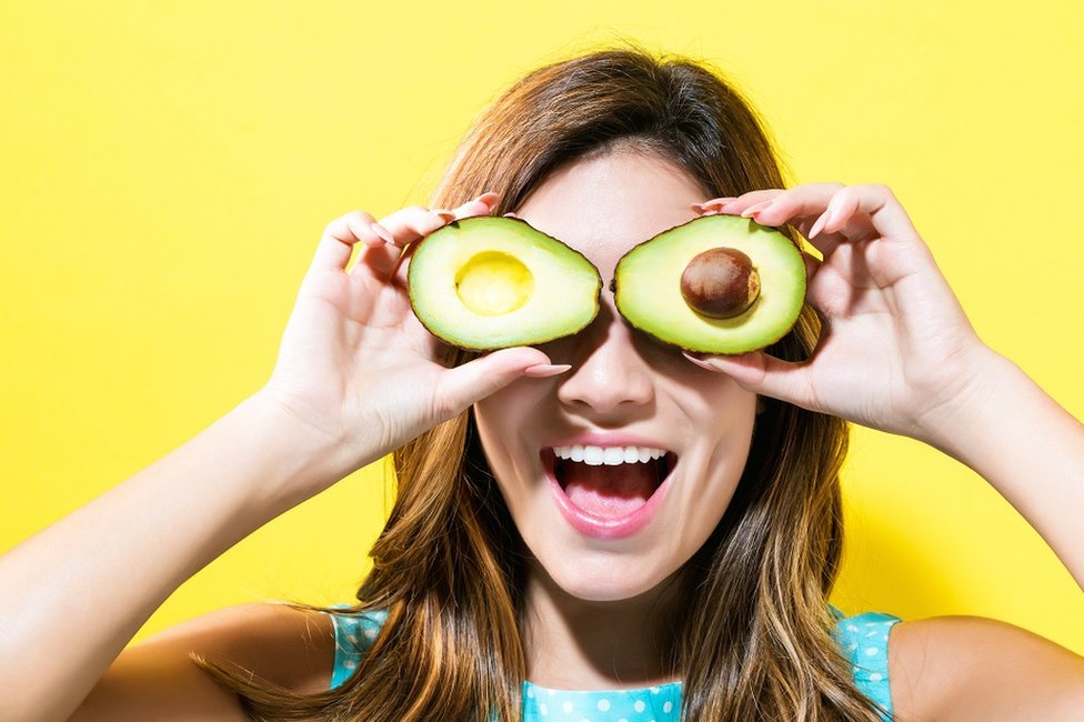 Happy young woman holding avocado halves - bright yellow background