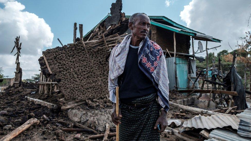 رجل يقف أمام منزله المدمر في قرية بيسوبر بمنطقة تيغراي الإثيوبية