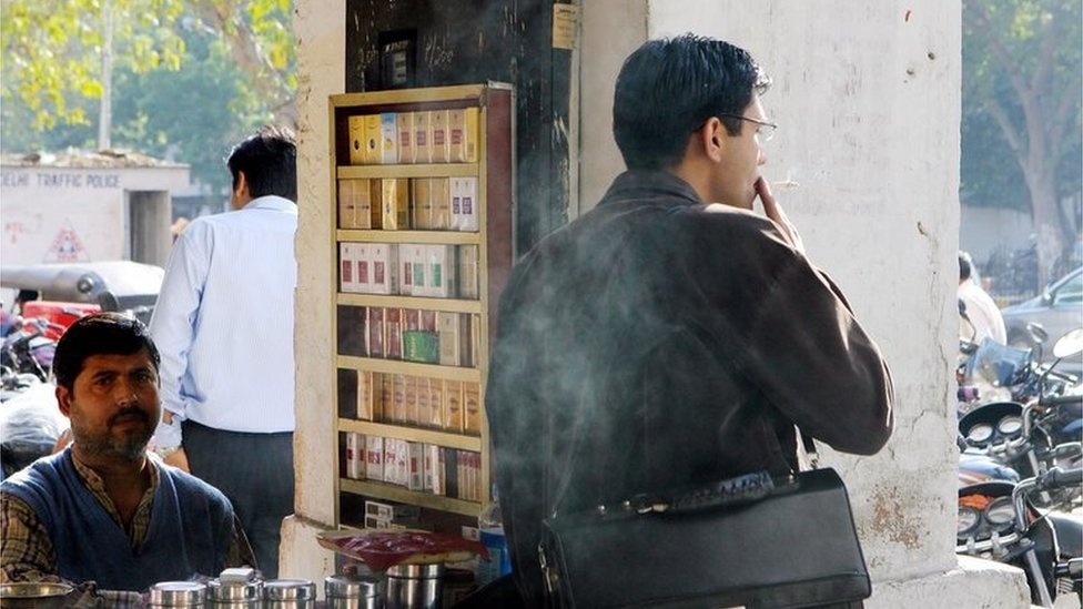 A cigarette vendor looks on as one of his customers smokes in Delhi (file photo)