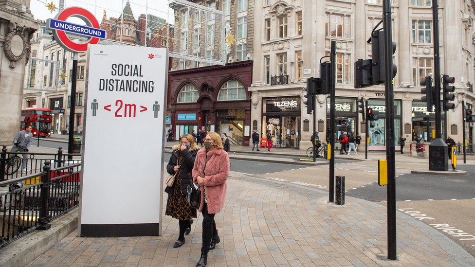 People wear masks next to a social distancing sign in London's Oxford Circus