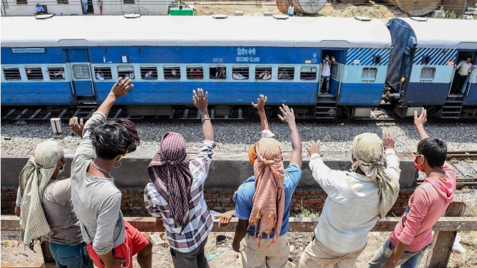 Radnici stoje pored voznog puta i mašu migrantima koji posebnim vozom odlaze iz Amritsara do Baraunija