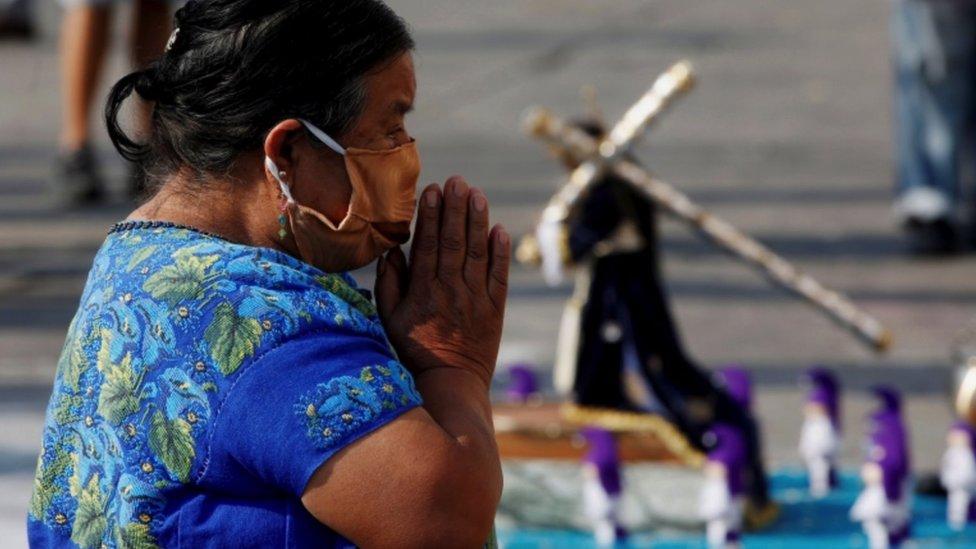 Guatemalteca rezando con mascarilla.