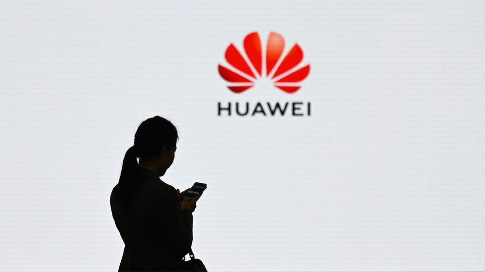 A Huawei logo is seen on the background as a staff member uses her mobile phone