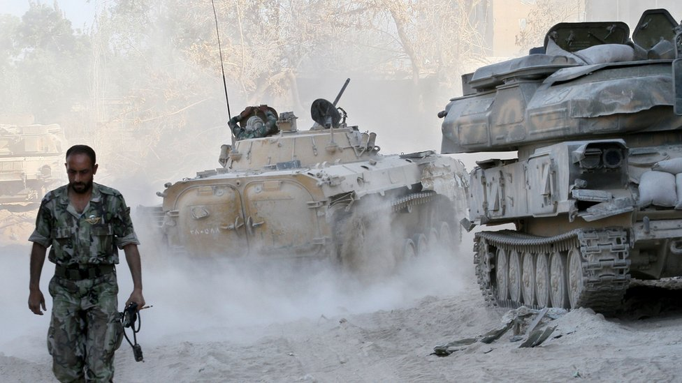 A Syrian army soldier walks past tanks in the Jobar neighborhood of Damascus, Syria, in 2013