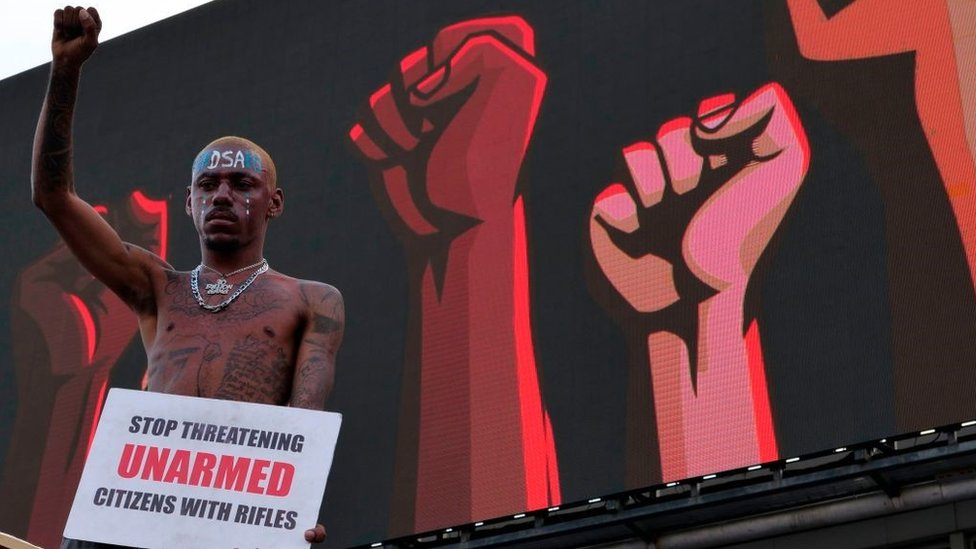 A protester gestures as he holds a placard at a live concert at the Lekki toll gate in Lagos, on October 15, 2020, during a demonstration to protest against police brutality and scrapping of Special Anti-Robbery Squad (SARS