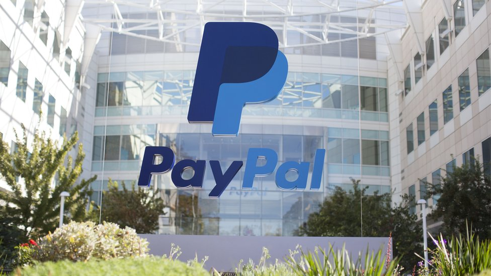 The PayPal logo is seen on a glass mount outside the company's offices in California