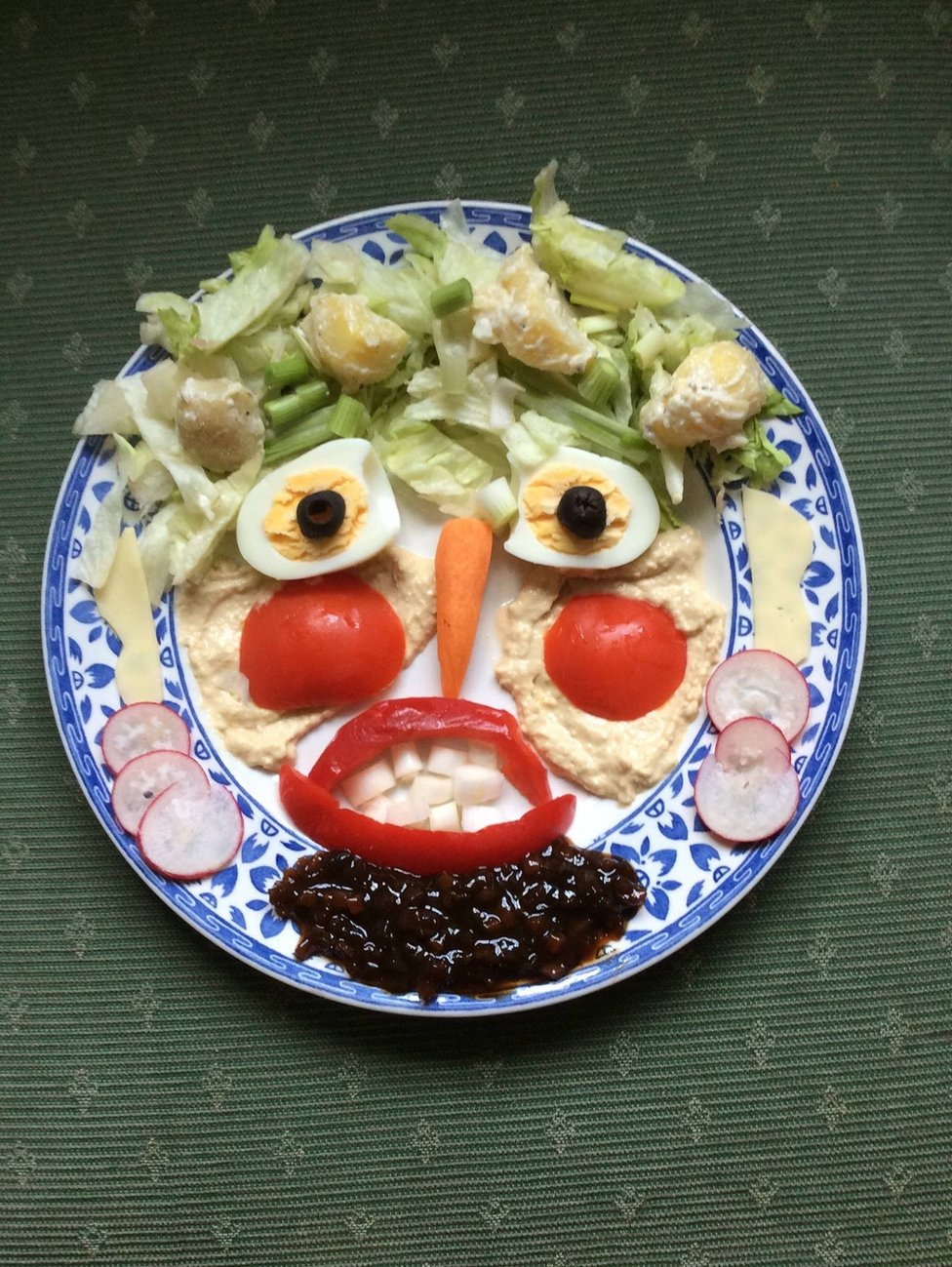 A salad has been put together to look like an angry face