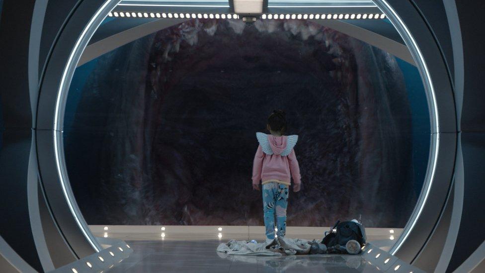 Una niña mira a través de una ventana las mandíbulas del Megalodón.