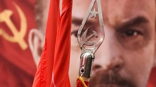 A picture of Vladimir Lenin behind a standard showing the communist symbol