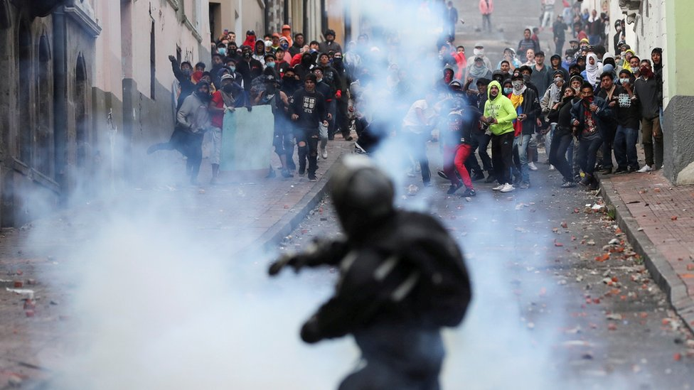 Un policía lanzando gases lacrimógenos a los manifestantes.