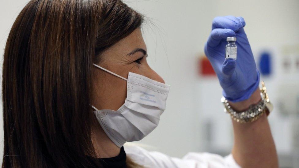 ممرضة تنظر إلى جرعة من اللقاح
