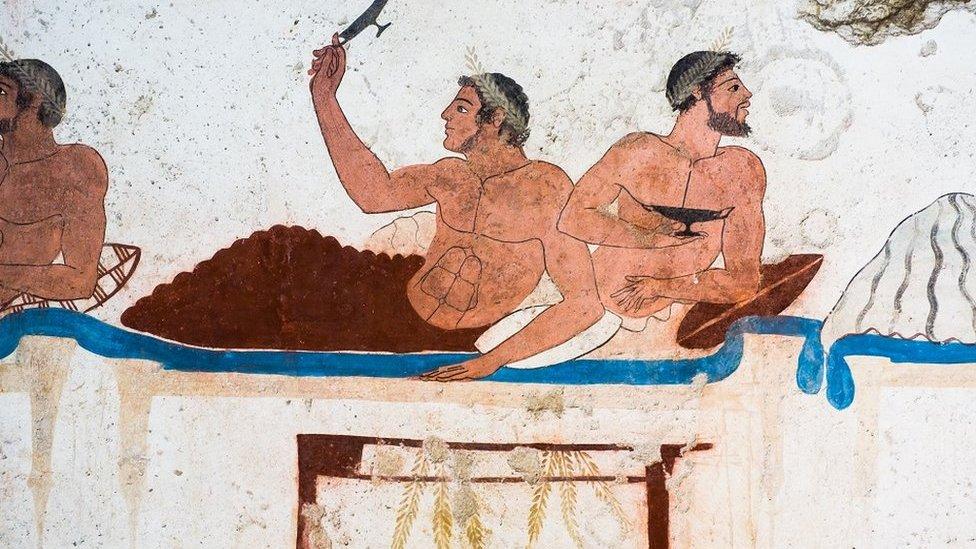 Stara freska iz Italije prikazuje dva muškarca kako uživaju u jelu u krevetu
