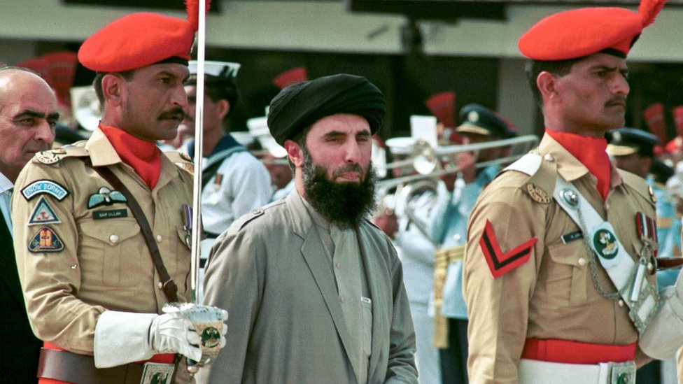Gulbuddin Hekmatyar, centre, passes in front of an honour guard in the Afghan capital of Kabul (26 June 1996)