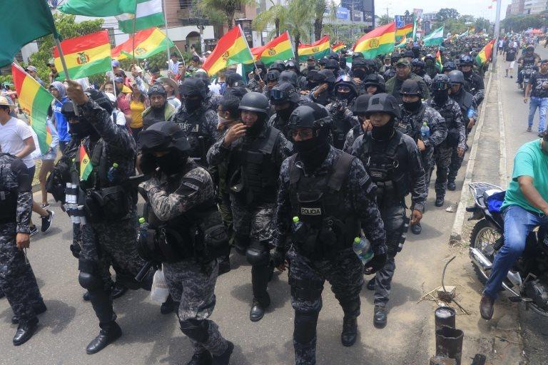 Santa Cruz şehrinde geri çekilen polis memurları Bolivya bayrağını sallıyor