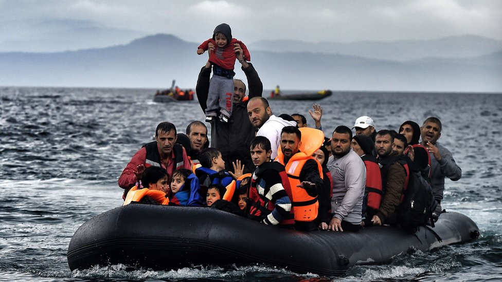 A man holds up a young boy as a boat carrying migrants and refugees arrives at the Greek island of Lesbos after crossing the Aegean sea from Turkey on October 21, 2015
