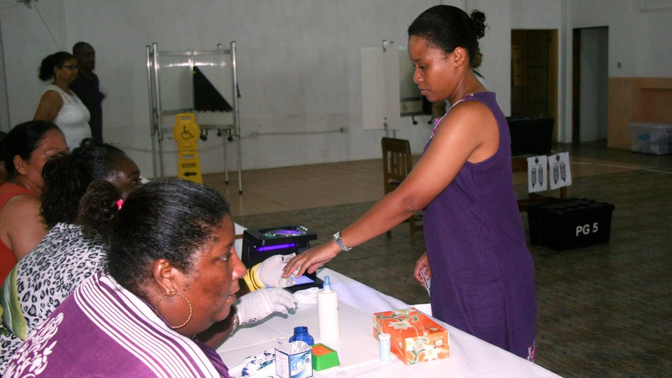A woman gives her fingerprint after voting at a polling station in Victoria, Seychelles, on 10 September 016