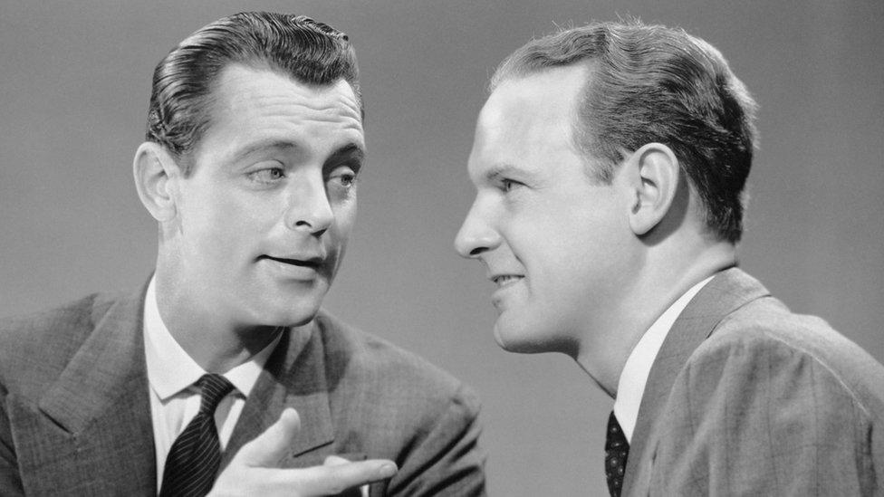 Dos hombres conversando en los 50.