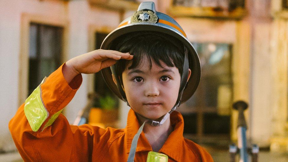 Niño con un traje de bombero.